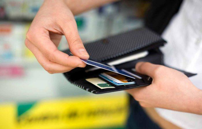 Достает кредитку из кошелька